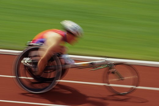 Wheelchair racer on track, side view : Stock Photo