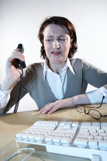 Stock Photo: 1598R-10618 Woman at desk holding telephone receiver