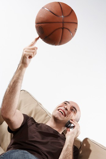 Man using mobile phone, spinning basketball, smiling, low angle view : Stock Photo