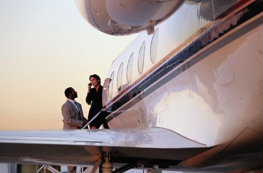 Businesspeople on the Steps of a Corporate Jet : Stock Photo
