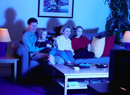 Family on a Couch Watching Television : Stock Photo