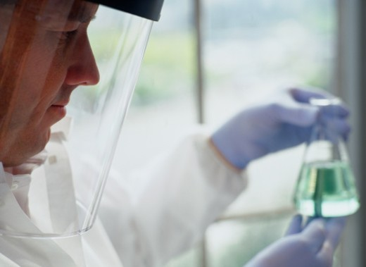 Chemist in a Protective Visor Examining a Flask : Stock Photo