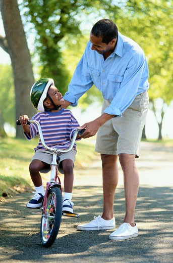 Stock Photo: 1598R-108096 Father Helping His Son Ride a Bicycle