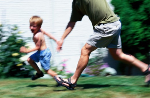 Boy and Man Playing Tag : Stock Photo