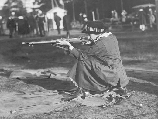 Woman crouching, aiming rifle (B&W) : Stock Photo