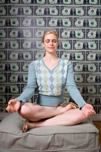 Stock Photo: 1598R-1163 Woman meditating in front of money papered wall