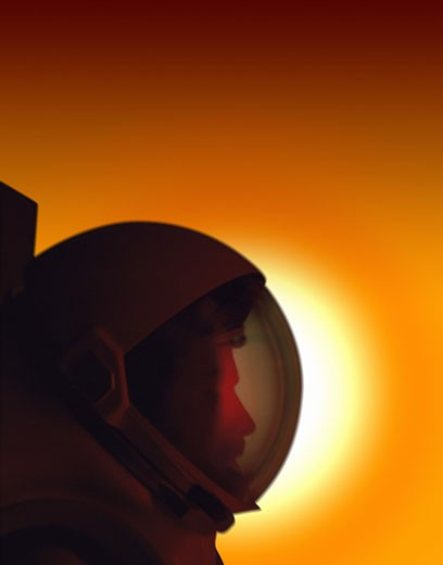 Stock Photo: 1598R-117141 Profile of a Helmeted Astronaut Against the Sun