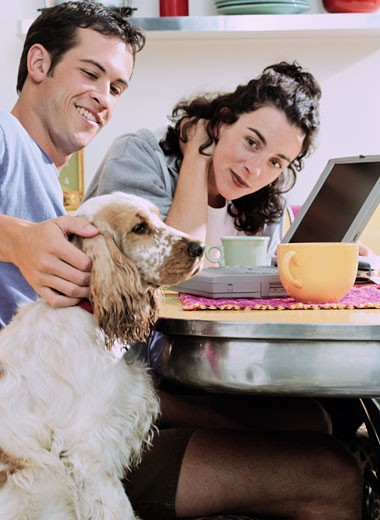 Couple at the Kitchen Table with Their Dog : Stock Photo