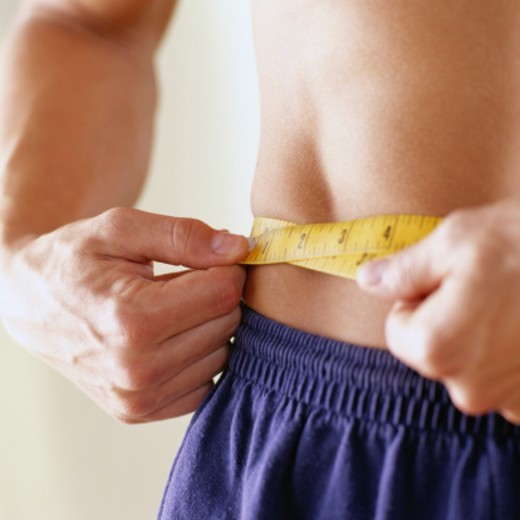 Stock Photo: 1598R-122074 Close-Up of a Man Measuring His Waist