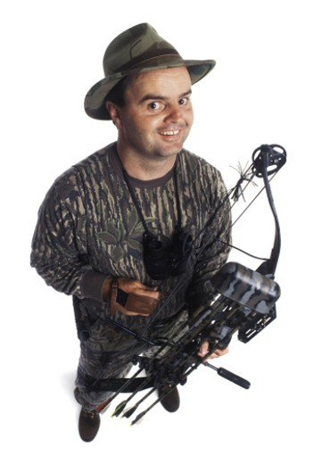 an adult male hunter dressed in camouflage and holding his crossbow smiles up at the camera : Stock Photo