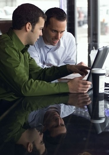 two young caucasian men look at a laptop computer and converse about its content : Stock Photo