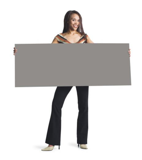 a young attractive african american girl in black pants and striped blouse holds a blank sign in front of her with both hands : Stock Photo