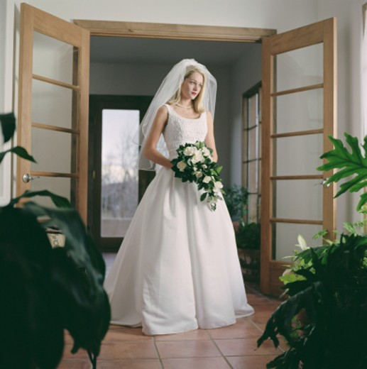 full body bridal portrait of a blonde woman in a wedding dress as she holds her floral bouquet : Stock Photo