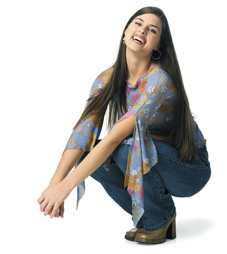 an attractive young caucasian woman crouches down and tosses up her head while laughing : Stock Photo