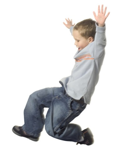 Stock Photo: 1598R-124440 full body shot of a young male child in a grey shirt as he jumps and glides through the air