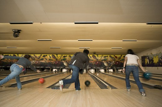 Rear view of three people bowling at a bowling alley : Stock Photo