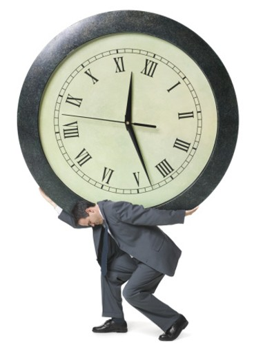 Man carrying a clock on his back : Stock Photo
