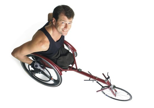 an adult caucasian male wheelchair racer in a black tank top smiles as he looks up at the camera : Stock Photo