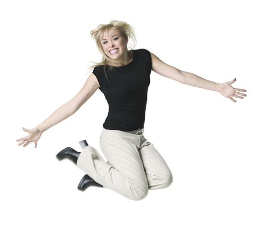 a young adult blonde female in tan pants and a black shirt jumps up and smiles : Stock Photo