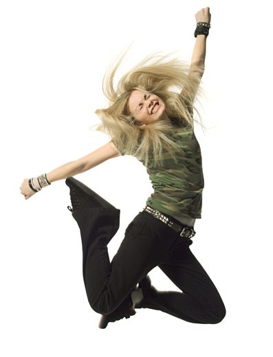 Stock Photo: 1598R-125149 a blonde female teen in black pants and a camouflage shirt jumps up wildly