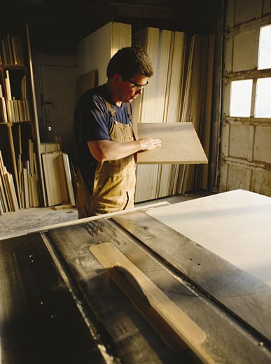 a caucasian  carpender inspects a rectangular board : Stock Photo