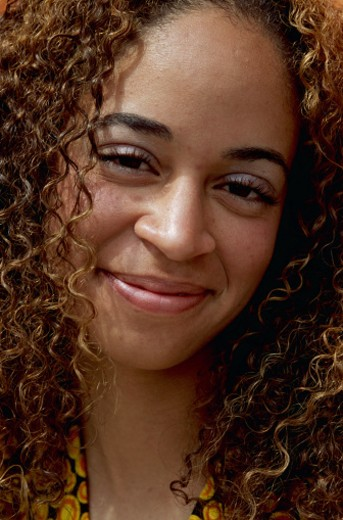 a head shot of a young african-american woman with long dark curly hair : Stock Photo