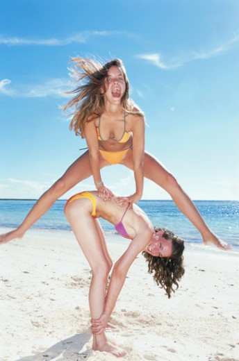 Stock Photo: 1598R-130620 Women playing leapfrog beach side