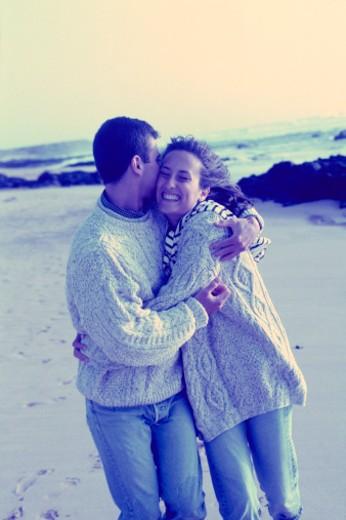 Couple embracing, walking along beach : Stock Photo
