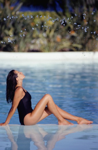 Young woman sunbathing in shallow water, side view : Stock Photo