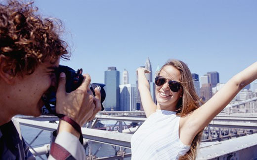 Young man taking photograph of young woman, New York City, USA : Stock Photo