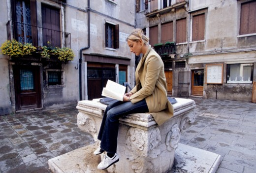 Stock Photo: 1598R-131616 Young woman reading book outside building, sitting on stone well