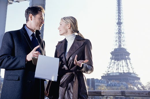 Paris, France, Two young businesspeople talking with clipboard : Stock Photo