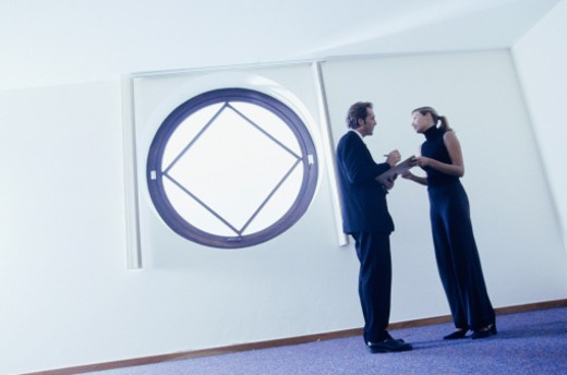 Businessman signing documents for businesswoman in hallway : Stock Photo