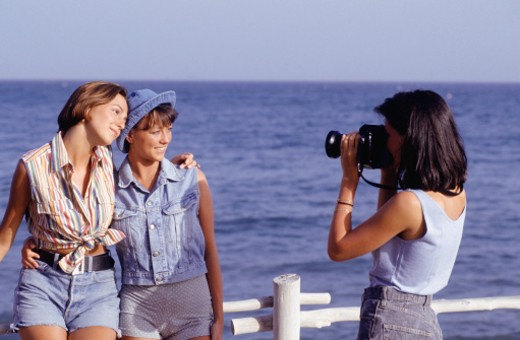 Woman photographing two women by ocean, three quarter length : Stock Photo