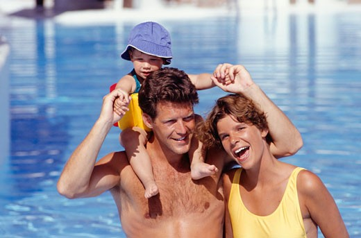 Stock Photo: 1598R-132125 Two parents in pool, father with baby boy (15-18months) on shoulders, portrait