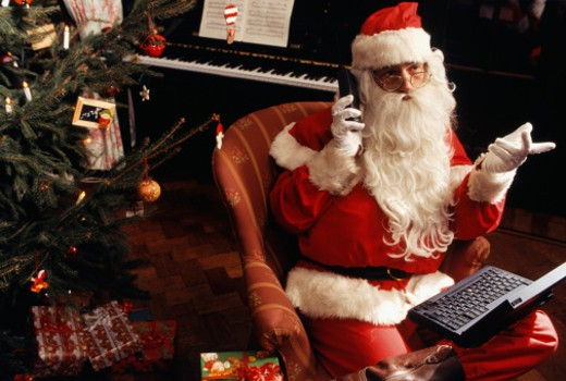Stock Photo: 1598R-132140 Santa Claus sitting in armchair with laptop and mobile phone