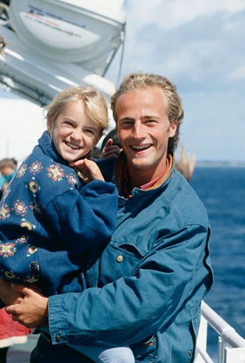 Stock Photo: 1598R-132316 Father holding daughter (10-11) on deck of ship