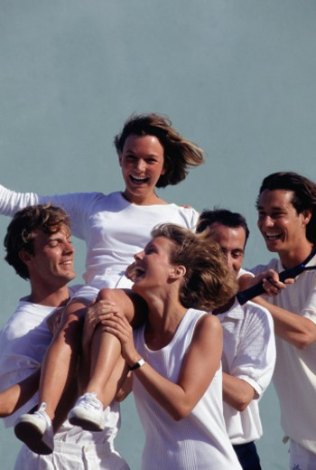 Group of tennis players carrying young woman on shoulders : Stock Photo