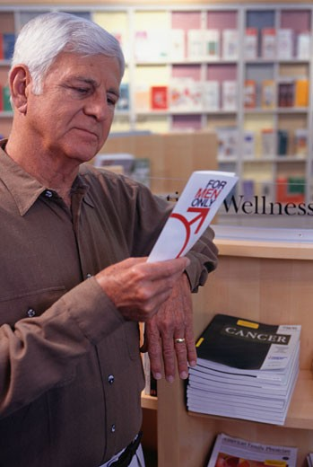Man in chemist looking at prostate brochure : Stock Photo