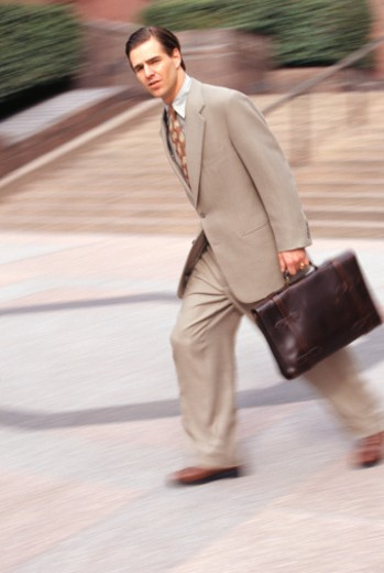 Businessman rushing with briefcase : Stock Photo