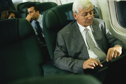 Businessman using laptop in airplane : Stock Photo