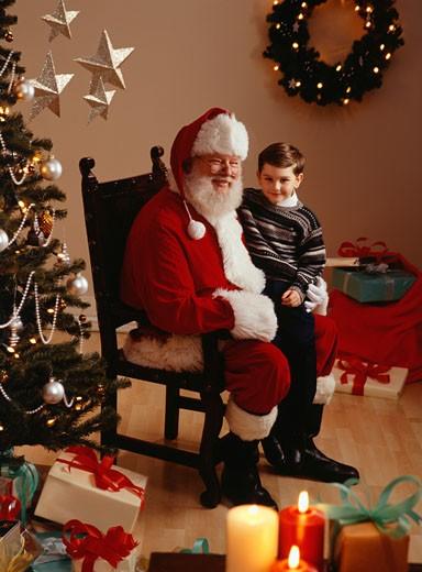 Boy (6-7) sitting on lap of Santa Claus, portrait : Stock Photo