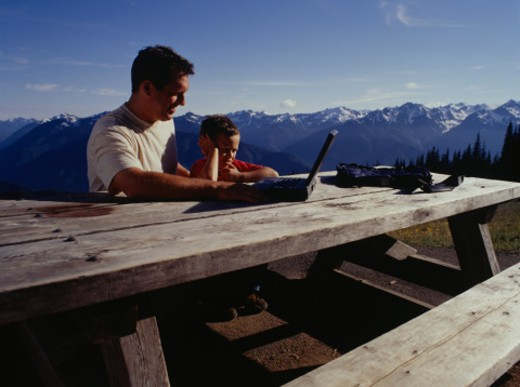 Father and son (3-4) using laptop on picnic table in mountain area : Stock Photo