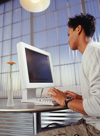 Young man using computer in Internet cafe, low angle view : Stock Photo