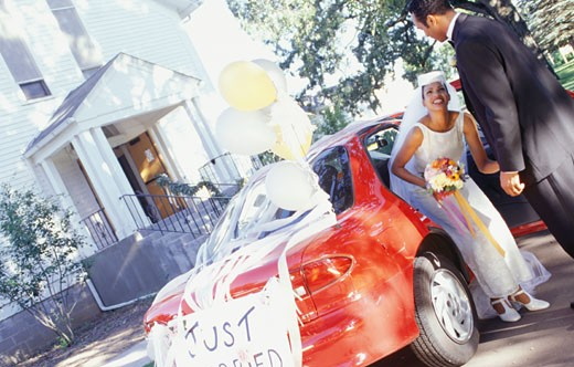 Stock Photo: 1598R-137268 Bride and groom getting out of car