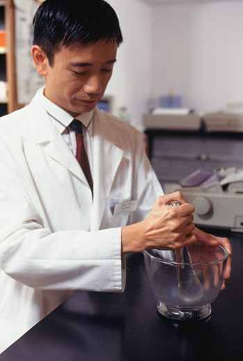 Stock Photo: 1598R-137516 Pharmacist in pharmacy using mortar and pestle