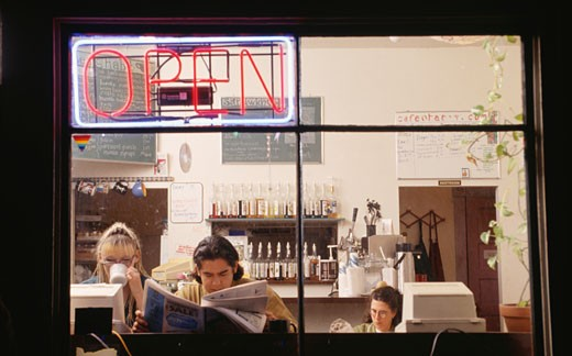 Stock Photo: 1598R-137679 Young people sitting in internet caf?, viewed through window