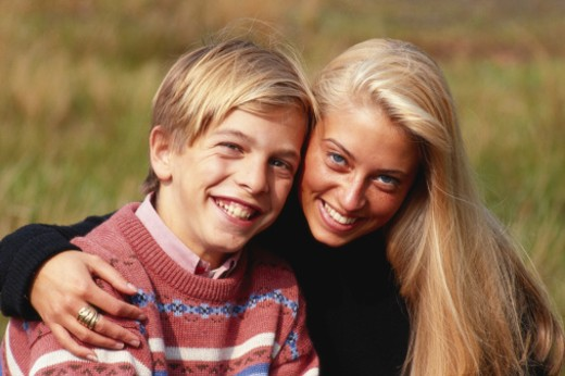 Boy (6-9) with mother smiling, close-up, outdoors : Stock Photo