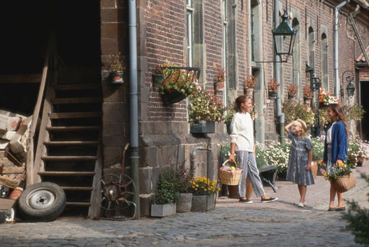Girl (6-7) with women in flower market : Stock Photo