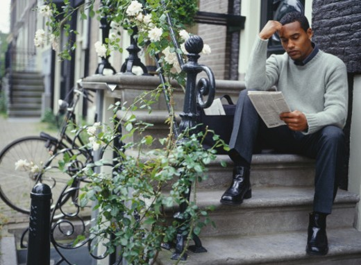 Young man reading newspaper on front steps outside house : Stock Photo